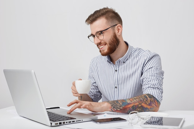 Indoor shot of creative business worker with tattooed arms, has thick beard