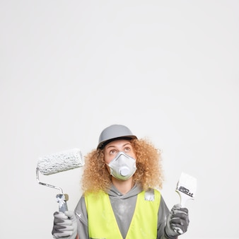 Indoor shot of curly woman maintenance worker looks attentively on ceiling