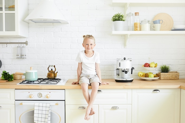Indoor shot of cute handsome little boy with blonde hair bun sitting on counter in stylish kitchen, hanging down his bare feet, waiting for mother to cook breakfast in the morning before school