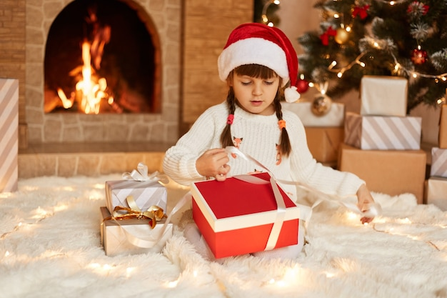 Indoor shot of cute little girl wearing white sweater and santa claus hat, sitting on floor near christmas tree, present boxes and fireplace, having concentrated expression while opening gift box.
