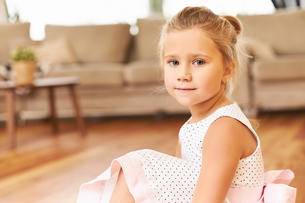 Indoor shot of cute little princess wearing beautiful pink dress sitting on floor at home getting ready for children's performance at kindergarten with adorable blue eyes