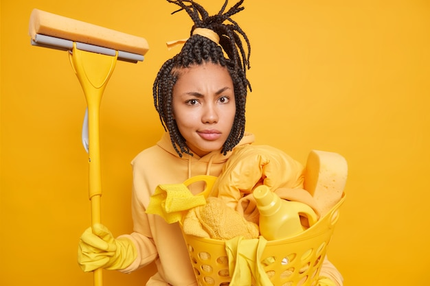 Indoor shot of dark skinned busy housemaid looks attentively holds mop basket of cleaning supplies and laundry dressed casually brings house in order isolated on yellow