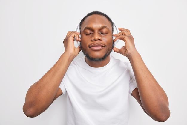 Indoor shot of dark skinned man closes eyes enjoys listening to  favorite lyrics song