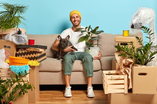 Indoor shot of delighted carefree house owner sits on couch and hugs pet