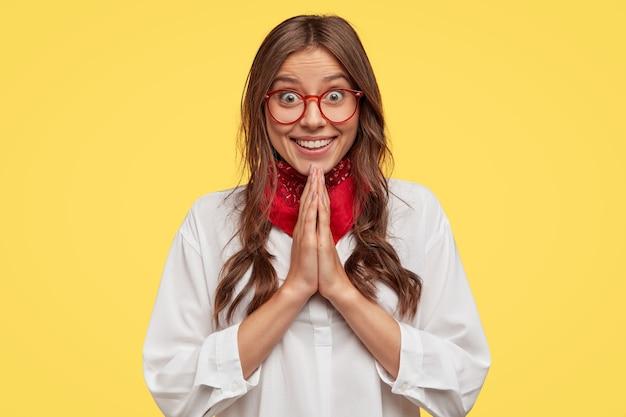 Tiro al coperto di donna felice felice ha un sorriso affascinante, tiene le mani in gesto di preghiera