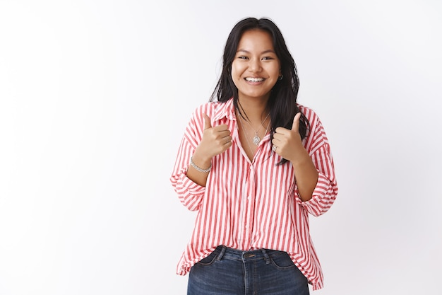 Indoor shot of delighted and impressed good-looking young asian female with dark hair in striped blouse showing thumbs up in like, recommend and approval, cheering over white wall