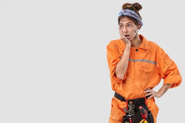 Tiro al coperto di una lavoratrice disperata sbalordita in posa contro il muro bianco