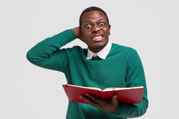 Indoor shot of displeased african american man clenches teeth and scratches head, holds textbook, puzzled with reading much information