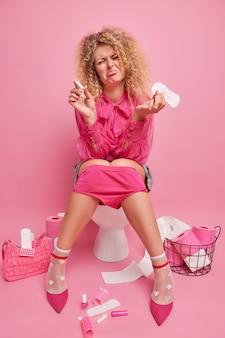 Colpo al coperto di dispiaciuta giovane donna dai capelli ricci tiene assorbente e tampone si sente male durante il periodo delle mestruazioni indossa camicetta rosa pantaloni scarpe tacco alto isolate su muro roseo