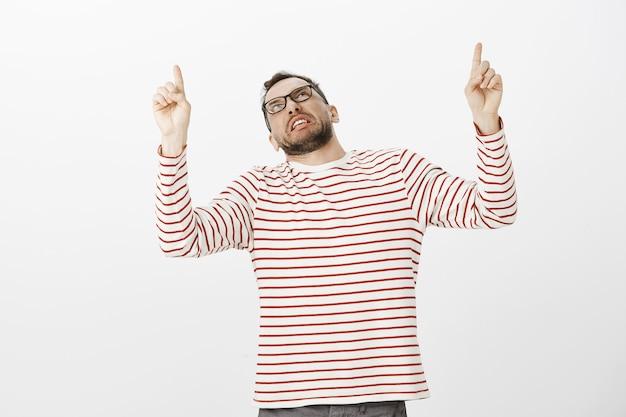 Tiro al coperto di un ragazzo adulto disgustato scontento in pullover a righe fantasia, indicando e guardando in alto con antipatia e antipatia