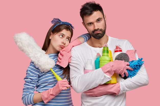 Indoor shot of displeased lady and male use rag, chemical detergents and brush for cleaning room, have dejected miserable exxpressions