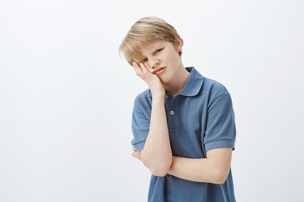 Indoor shot of displeased unhappy young boy with blond hair in blue t-shirt, making face palm and grimacing, being annoyed or fed up with homework