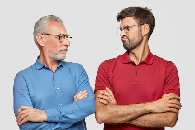 Indoor shot of displeased young male looks at his grandfather, keeps hands crossed, have talk about life, stand next to each other, isolated over white wall. people, communication concept