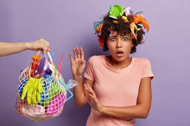 Tiro al coperto di donna afroamericana insoddisfatta fa il gesto protettivo contro il sacchetto netto con immondizia di plastica