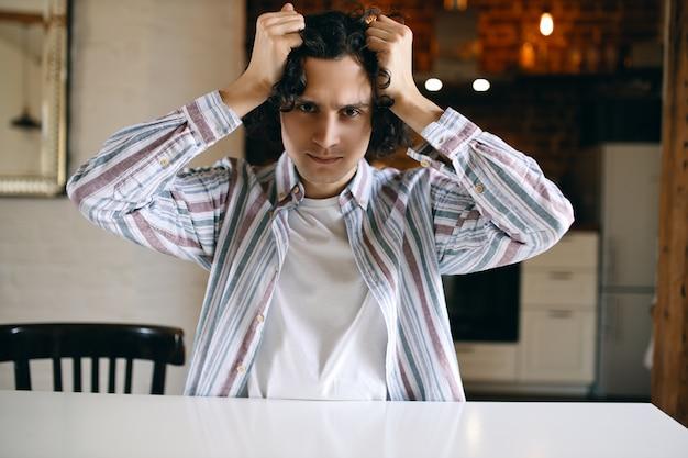 Tiro al coperto di giovane maschio arrabbiato insoddisfatto che strappa i capelli stressato a causa di cattive notizie, crisi economica, pandemia, sensazione di impotenza, deve rimanere a casa.