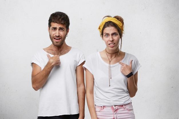 Tiro al coperto di maschio e femmina insoddisfatti che indossano abiti casual che aggrottano le sopracciglia e indicano con le dita se stessi perplessi per essere scelti. coppie europee che hanno sguardo confuso