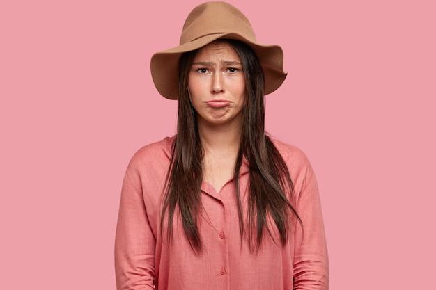 Tiro al coperto di donna insoddisfatta ha un'espressione facciale placida di scontento, increspa le labbra per il dispiacere, essendo di umore basso
