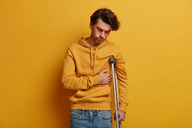 Indoor shot of distressed man has broken rib, suffers from pain, stands on crutches, had accident on road, wears yellow sweatshirt, has illness and injury, poses over yellow wall. mobility aid