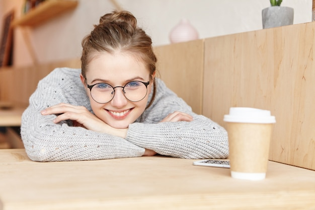 Indoor shot of dreamy adorable woman wearing round spectacles