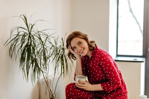 Indoor shot of dreamy woman in pajama drinking tea. smiling caucasian young woman holding cup of coffee.