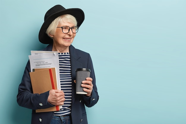 Indoor shot of elderly lady in high spirit, finishes paper work has coffee break, wears hat and jacket, looks aside, sees something pleasant. experienced mature female teacher poses over blue wall