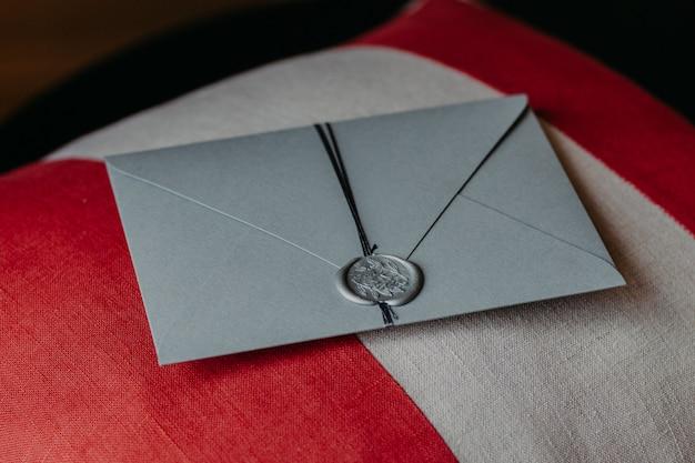 Indoor shot of elegant grey paper invitation card lies on sofa pillow.