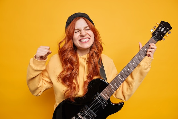 Indoor shot of emotional ginger teenage girl clenches fist and teeth wears black hat hoodie keeps eyes closed being rock n roll star celebrity plays music on black electrical guitar yellow wall
