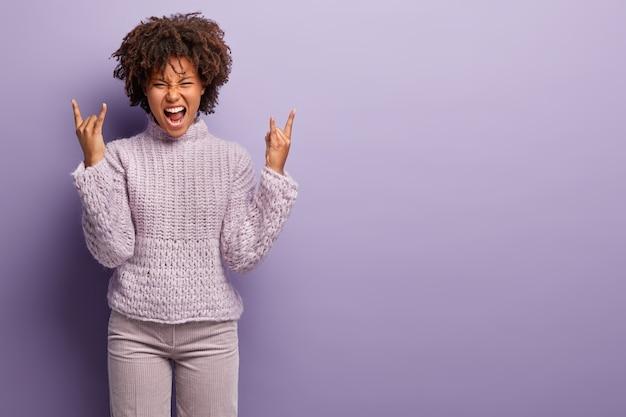 Ripresa interna di una signora emotiva con acconciatura afro, fa il gesto del rock n roll, esclama, si sente felicissima, gode di una festa a tema musicale, indossa maglione e pantaloni, isolato su un muro viola, spazio libero