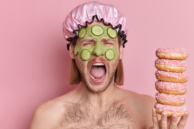 Indoor shot of emotional man exclaims loudly opens mouth undergoes skin care treatments applies green clay mask with cucumber slices holds pile of doughnuts.