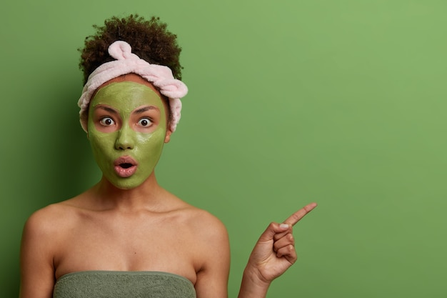 Indoor shot of emotional surprised woman does beauty procedures, applies facial mask for rejuvenation, demonstrates something shocking on empty space, green wall. skin care, wellness concept