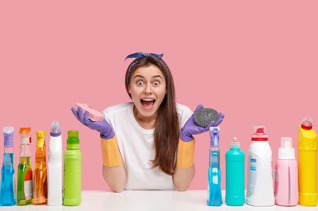 Tiro al coperto di bella donna emotiva stupita tiene le spugne, usa i prodotti per la pulizia per la salatura della casa in ordine