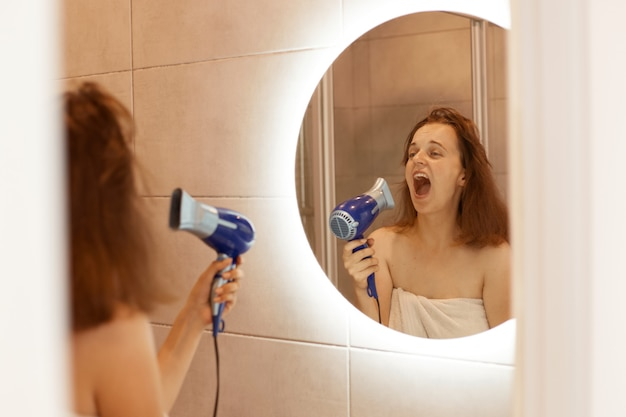 Indoor shot of excited happy young adult woman drying hair in bathroom with hair dryer, looking at reflection in the mirror and singing, keeps mouth opened.