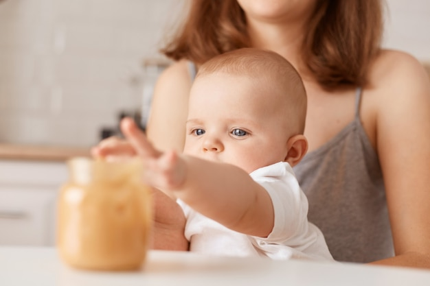 Indoor shot of faceless mother feeding her little infant daughter with vegetable puree, charming toddler baby stretching hand to jar with food, feeding up.