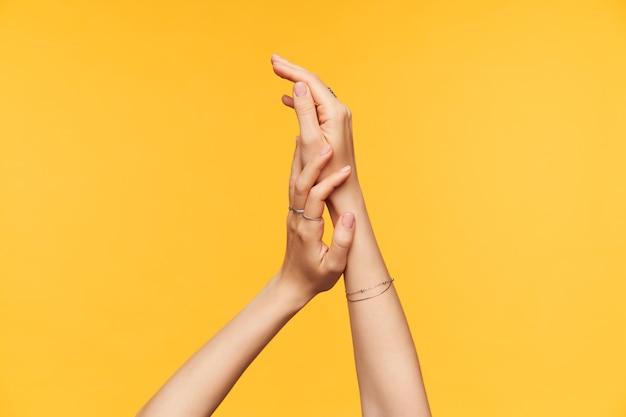 Tiro al coperto di mani dalla pelle chiara della giovane donna che si toccano delicatamente mentre si applica la crema su di esso, isolato su sfondo giallo. concetto di cura del corpo e delle mani