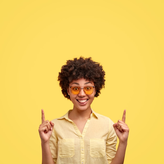 Indoor shot of fashionable black woman has afro hairstyle, wears trendy shades, shirt in one tone with wall, smiles positively, indicates upwards shows free space above head. use this for advert