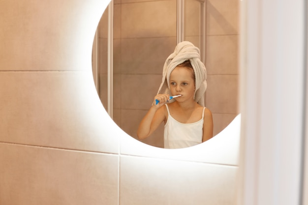Indoor shot of female child brushing teeth in bathroom, looking at her reflection in the mirror, wearing white t shirt and wrapped her hair in towel, hygienic procedures.
