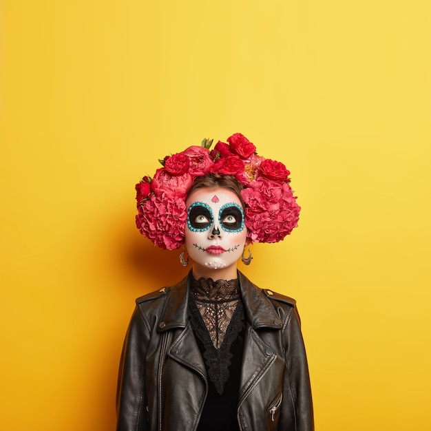 Indoor shot of female model has artistic designed face, wears professional horror makeup for halloween holiday, dressed in special costume, focused upwards, isolated over yellow wall. copy space
