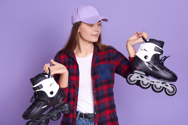 Indoor shot of female posing against lilac studio wall with rolling skates in hands