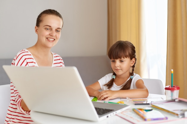 Indoor shot of female with little girl, child wearing white t shirt and has pigtails, people looking at laptop screen, kid having online lesson during quarantine, mother helping her.
