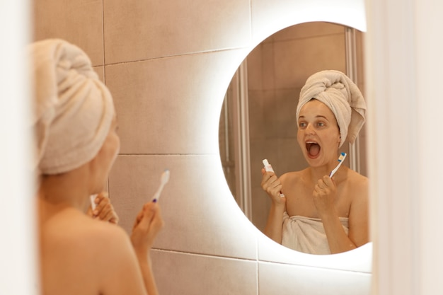 Indoor shot of female with white towel on her head holding toothpaste and toothbrush in hands, looking at her reflection in the mirror with widely open mouth.