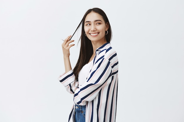 Indoor shot of feminine flirty fashionable woman in striped blouse, turning right while playing with hair strand and smiling joyfully, being satisfied with finished design project over gray wall