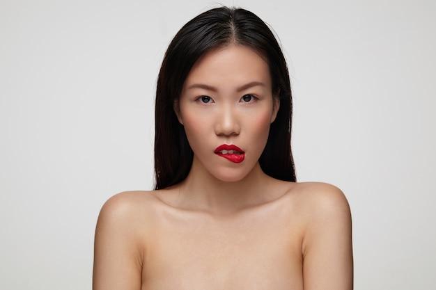 Tiro al coperto di flirty giovane donna bruna dagli occhi marroni con trucco festivo che si morde il labbro inferiore mentre guarda giocosamente, isolato sopra il muro bianco