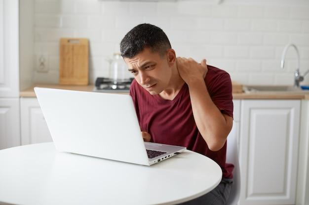 Colpo al coperto di lavoratore maschio freelance seduto in cucina al tavolo davanti al taccuino bianco, guardando attentamente il display del laptop cercando di notare cosa importante, tiene la mano sul collo.