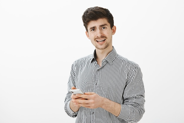 Indoor shot of frustrated displeased mature guy with moustache in casual striped shirt, looking questioned while asking question and holding smartphone, receiving confusing message