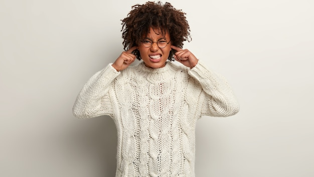 Indoor shot of frustrated woman with dark skin, curly hair, plugs ears, clenches teeth, avoids bad sound or noise, has dissatisfied expression, wears white knitted jumper, isolated over white wall