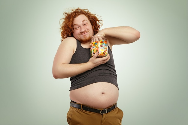 Indoor shot of funny redhead young male, grasping handful of candies out of glass jar