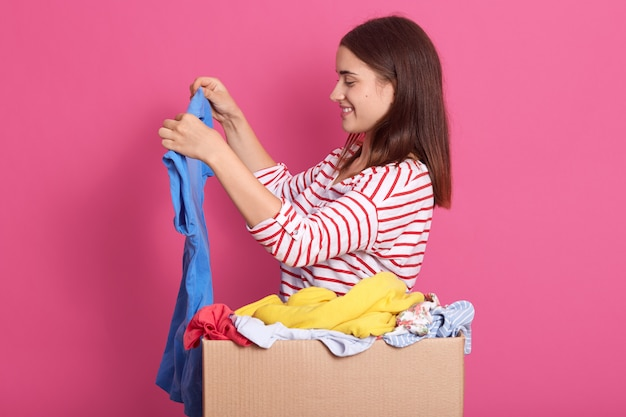 Indoor shot of girl stands with blue shirt near cardboard box full of fashionable clothes, lady wearing striped shirt