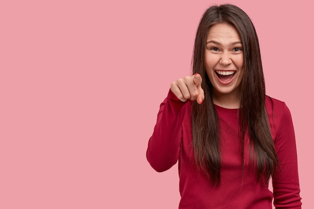 Indoor shot of glad young european woman smiles gladfully, points at camera with index finger, chooses you