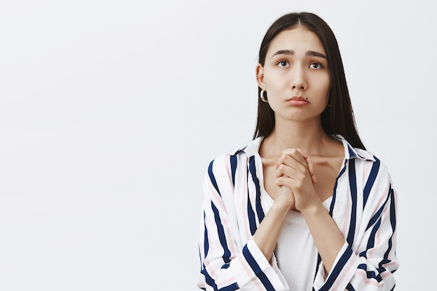 Indoor shot of gloomy cute female in striped blouse over t-shirt, clasping hands and pursing lips, frowning while gazing up with hopeful expression, waiting for results of test over gray wall