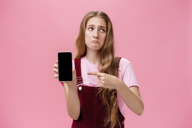 Ripresa in interni di una ragazza carina, triste e delusa, che tiene in mano uno smartphone che punta al cel...